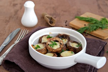 Hot appetizer, baked mushrooms with suluguni cheese in white ceramic form. Georgian cuisine.