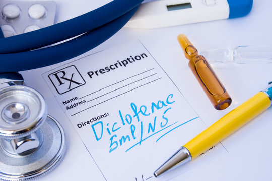 Recipe written out of anti-inflammatory medication Diclofenac in form of International Nonproprietary Name (INN) or generic name is on doctor table near vials of medicine and diagnostic tools