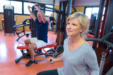 senior woman in gym working out with weights