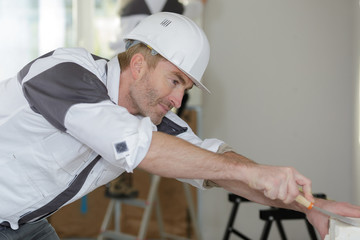 happy builder in hardhat plastering a wall