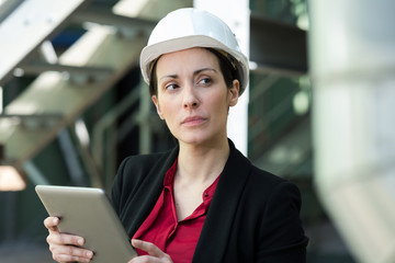 female of female professional in the factory holding tablet