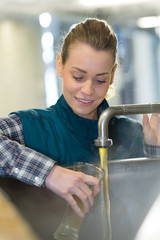 beer brewery worker taking sample