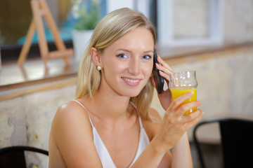 young woman posing holding a glass of juice