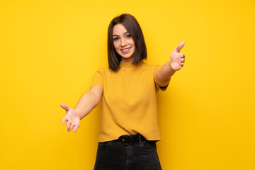 Young woman over yellow wall presenting and inviting to come with hand