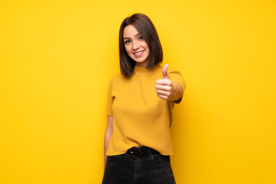 Young woman over yellow wall with thumbs up because something good has happened