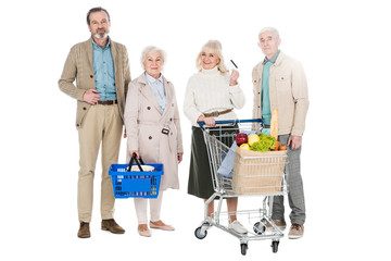 cheerful senior friends standing with basket and shopping cart isolated on white