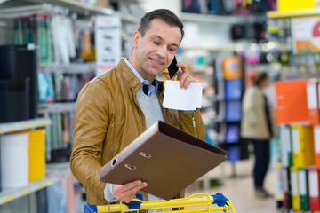 man calling on cell while holding a folder