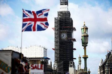 A souvenir Union Jack flags flies in the wind as Big Ben can be seen in the background in London