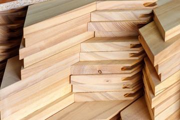 The stack of wooden blanks for furniture manufacturing in the carpenter workshop. Soft focus