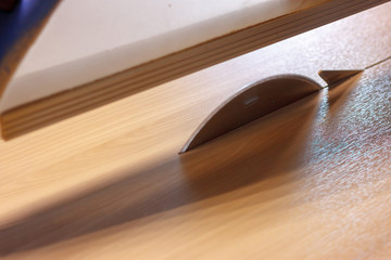The sawing of the big wood panel on the circular saw table tool. Wooden furniture production on the carpenter manufacture. Soft focus