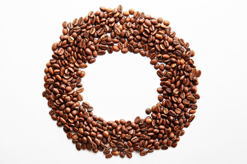 Roasted brown coffee beans scattered on white table with a lot copy space for text. Flat lay composition. Close up, top view, background.