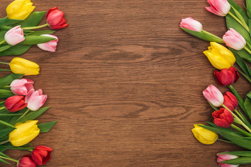 top view of colorful tulips on wooden background with copy space