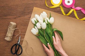cropped view of on florist making bouquet of white tulips on wooden background