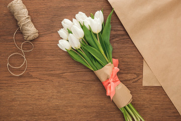 top view of spring tulip bouquet and craft paper on wooden background