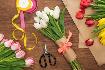 top view of spring tulip bouquet, ribbons and craft paper on wooden background