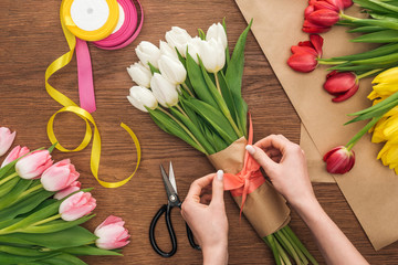 cropped view of on female florist making bouquet of spring tulips on wooden background