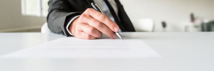 Wide view image of businessman sitting at his office desk signing a document