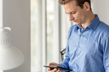 Young businessman looking at digital tablet