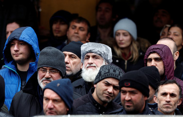 People watch as rescue workers work at the site of a collapsed residential building in the Kartal district, Istanbul