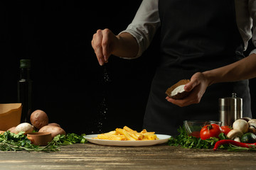 Chef salting french fries ready, on the background with vegetables. Cooking tasty but harmful food. Background for design and menu, homemade recipe, cookbook. Fast food