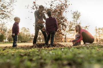 Young family having fun in a park throwing autumn leaves