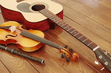 Guitar, violin, pipe on a wooden table
