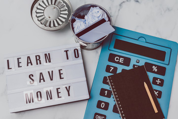 lightbox with Learn to save money message with payment card in the trash and stationery on marble desk