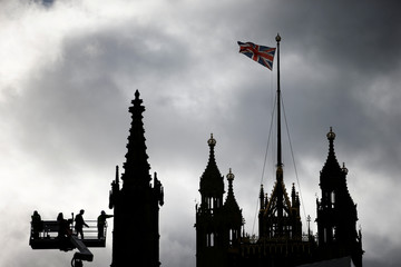Workers using a crane can be seen inspecting part of the roof of the Houses of Parliament in London