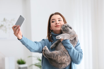 Young woman taking selfie with her cute cat at home