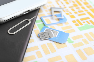 Sim cards with passport and mobile phone on map