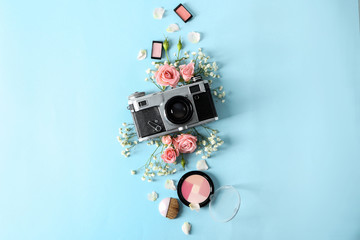 Composition with photo camera and makeup cosmetics on color background