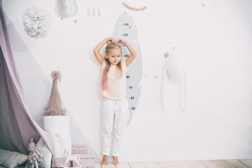 Little beautiful child girl in the children's playroom measures her height
