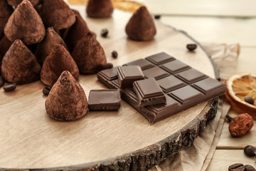 Wooden board with tasty sweet truffles on table, closeup