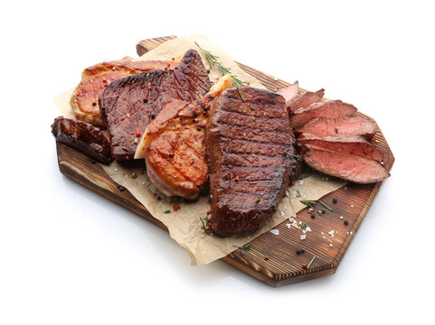 Wooden board with different tasty cooked meat on white background