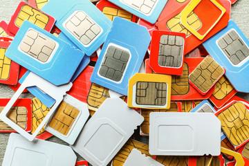 Many sim cards on grey background, closeup