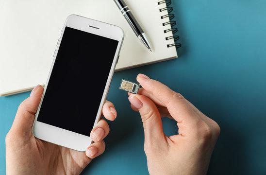 Woman inserting sim card into mobile phone, closeup