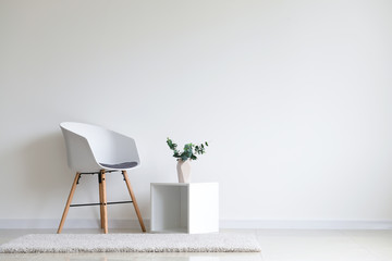 Stylish chair with shelf near white wall in room