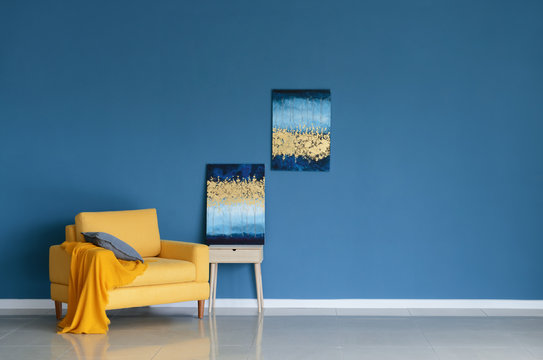 Bright armchair with pictures near color wall in room