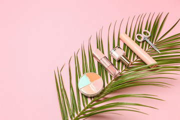 Set of makeup cosmetics with palm leaf on color background