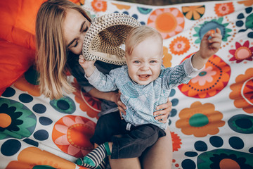 Young family portrait of a beautiful hipster mother with cute blonde boy with blue eyes and vintage hat sitting on a boho hammock outdoors, family camping vacation concept