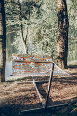 Stylish polka dot hammock near lake at summer vacation camp, boho hammock hanging outdoors, family camping trip concept
