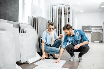 Beautiful young couple choosing big granite tiles for their house repairment in the building shop Fototapete