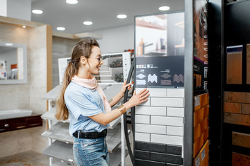 Young woman designer choosing ceramic tiles looking on the exposition in the shop