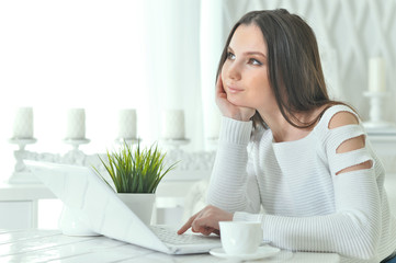 Portrait of young woman using modern laptop at table