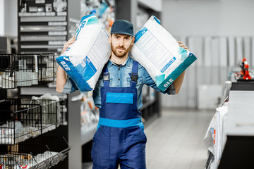 Portrait of a handsome workman in blue overalls holding bags with construction mixture in the building supermarket