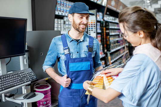 Young woman client choosing paint from color swatches, standing with workman in supermarket with building goods