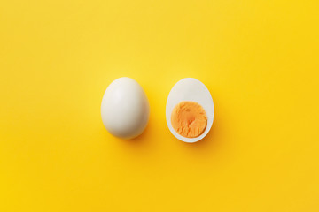 Single whole white egg and halved boiled egg with yolk on a yellow background. Top view Wall mural