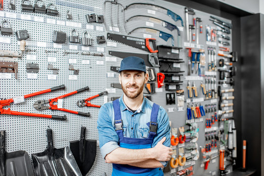 Portrait of a handsome worker in uniform standing in the shop with garden equipment on the background