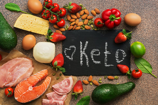 Keto diet food. Healthy low carbs products.Keto diet concept. Vegetables, fish, meat, nuts, seeds, strawberries, cheese on a brown background. Top view. Signboard.
