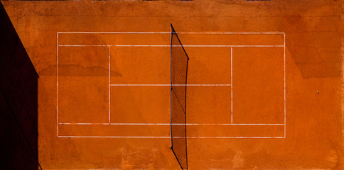 Aerial view of an empty tennis court at sunset